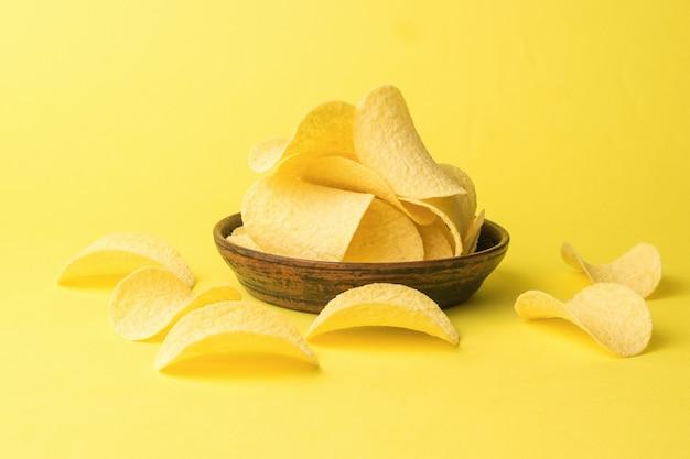 Een kleikom vol met chips op een gele achtergrond. een populair aardappelgerecht.