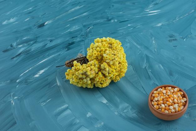 Een kleikom vol ongekookte maïszaden met een boeket bloemen.
