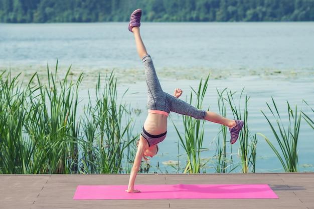 Een klein acrobaatmeisje staat op haar handen en doet de acrobaattruc in de lucht op een pier bij het meer