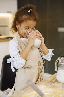 Een klein afro-amerikaans meisje drinkt een glas melk, die ze in een glazen kom moet gieten en een deeg moet bereiden.