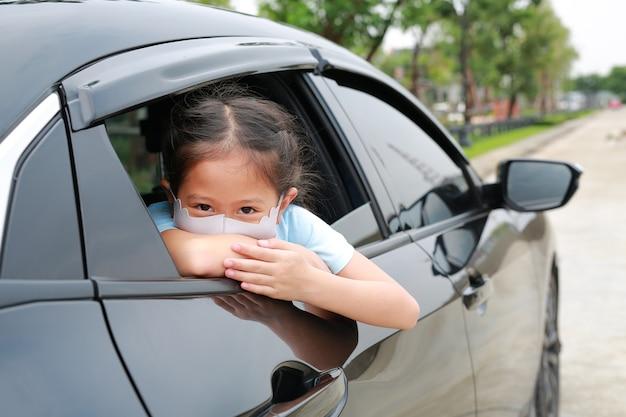 Een klein aziatisch meisje draagt een hygiënisch gezichtsmasker dat door de camera kijkt en haar hoofd uit het autoraam steekt