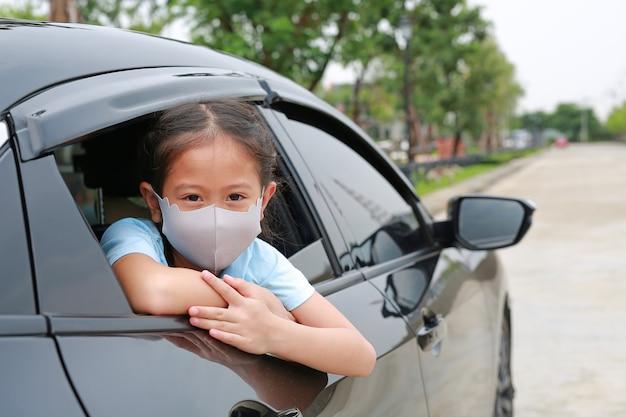 Een klein aziatisch meisje met een hygiënisch gezichtsmasker steekt haar hoofd uit het autoraam tijdens de uitbraak van het coronavirus (covid-19)