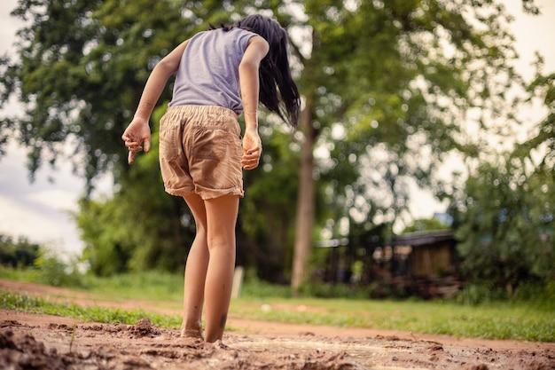 Een klein aziatisch meisje speelt overdag met aarde in de natuur bij hem thuis.