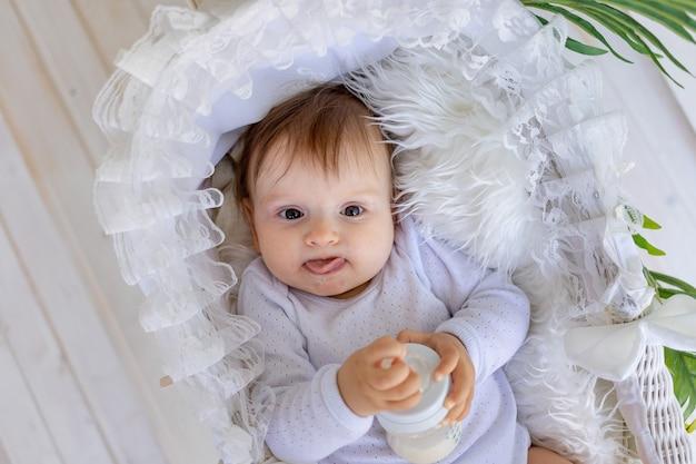 Een klein babymeisje ligt thuis in een mooie wieg in een wit rompertje en heeft een fles melk in haar handen