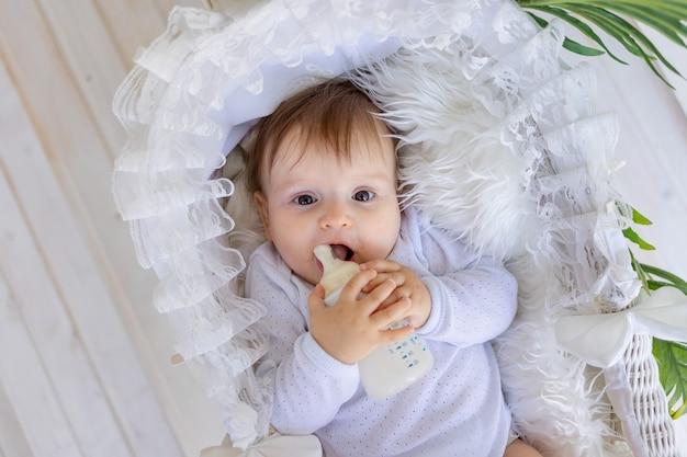 Een klein babymeisje ligt thuis in een mooie wieg in een wit rompertje en heeft een fles melk in haar handen Premium Foto