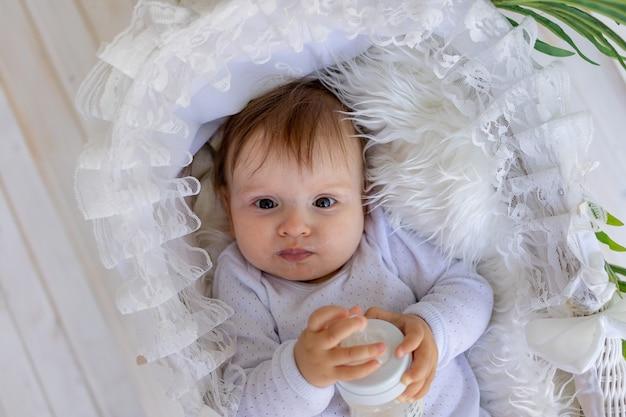 Een klein babymeisje ligt thuis in een mooie wieg in een wit rompertje