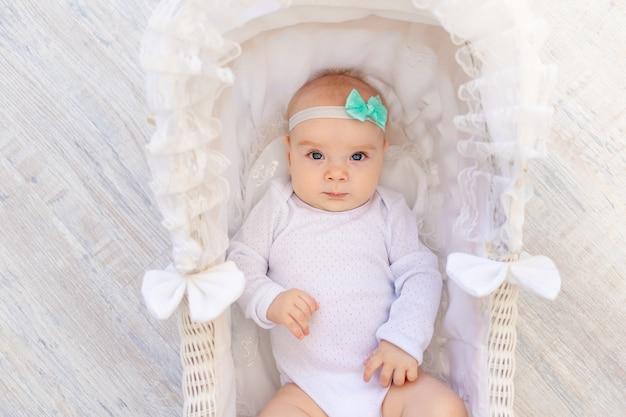 Een klein babymeisje van 6 maanden oud in een wit rompertje ligt in een prachtig wiegje