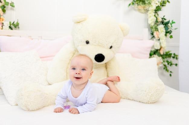 Een klein babymeisje van 6 maanden oud ligt thuis op een wit bed met een grote teddybeer
