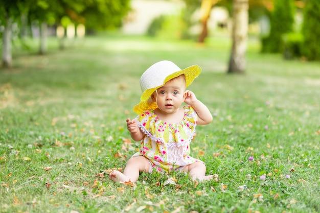 Een klein babymeisje van 7 maanden zit op het groene gras in een gele jurk en hoed en houdt haar hand tegen haar oor