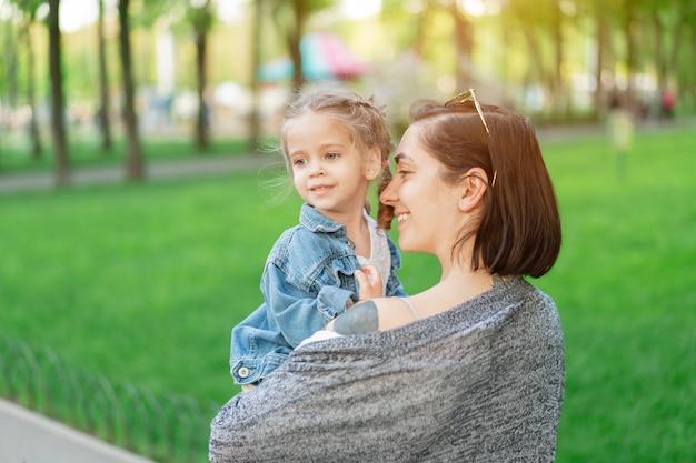 Een klein blank meisje gekleed in een spijkerjasje zit in de armen van haar moeder. moeder en dochter golf in het park op een warme zomerdag