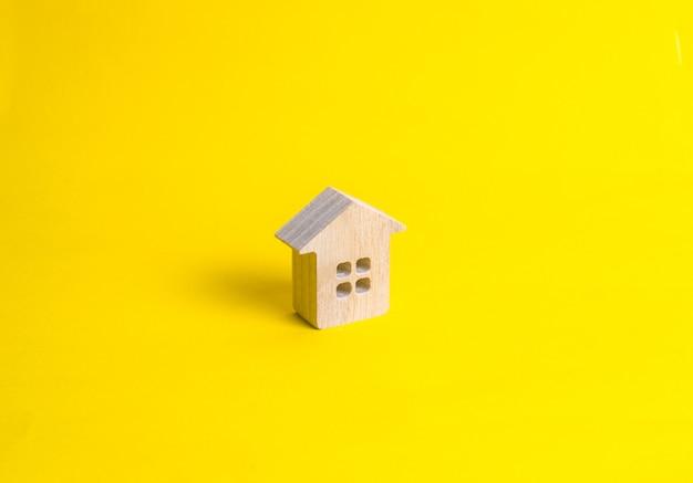 Een klein blokhuis staat op een gele achtergrond.