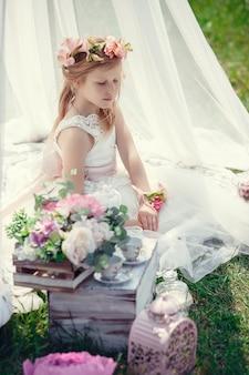 Een klein blond europees meisje in een mooie jurk poseert in de buurt van het landschap in het veld. baldakijn, bloemen, tederheid, krans,