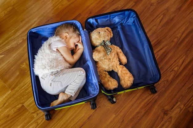 Een klein blond meisje droomt van reizen en liggen in een koffer met teddybeer