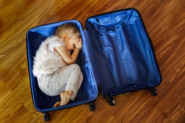 Een klein blond meisje droomt van reizen en liggen in een koffer