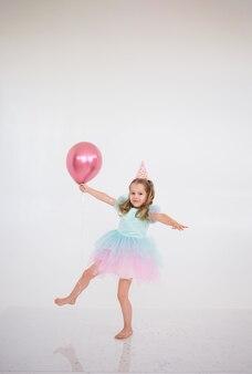 Een klein blond meisje in een elegante jurk danst met een roze ballon op een witte achtergrond met een plek voor tekst