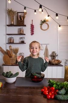 Een klein blond meisje in een groene trui zit aan een houten tafel en bereidt een groentesalade