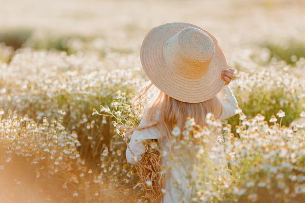 Een klein blond meisje in een pofjurk en strohoed kijkt naar het veld met madeliefjes, het uitzicht van achteren. ruimte voor tekst