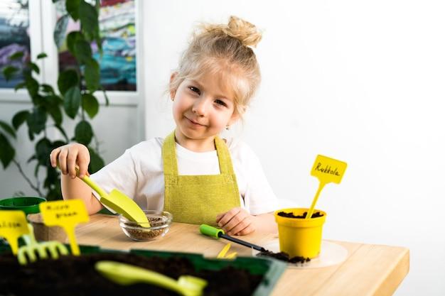 Een klein blond meisje in een schort houdt zich bezig met het planten van zaden voor zaailingen, glimlachend, het concept van tuinieren voor kinderen.