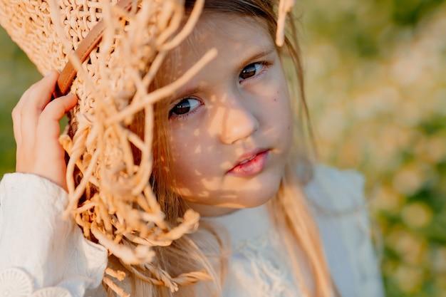 Een klein blond meisje in een strooien hoed in de zomer bij zonsondergang