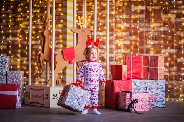 Een klein blond meisje in kerstpyjama houdt een geschenk vast tegen de achtergrond van de carrousel. hoge kwaliteit foto