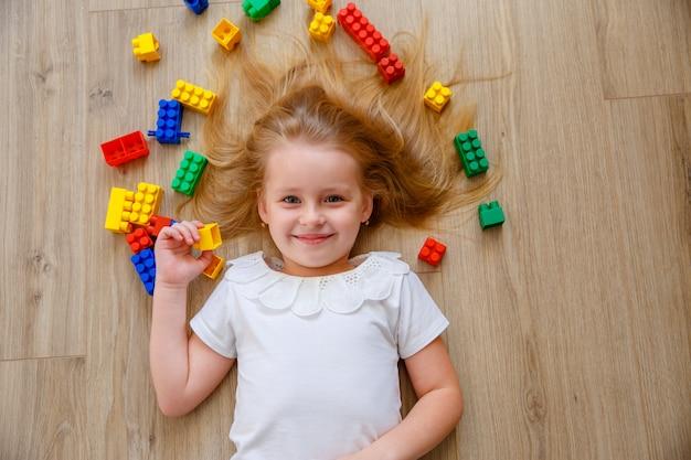 Een klein blond meisje ligt op de vloer tussen de constructeur. het uitzicht vanaf de top.