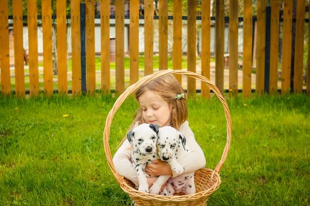Een klein blond meisje met haar huisdierenhond outdooors in park.