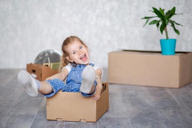 Een klein blond meisje speelt thuis in quarantaine met kartonnen dozen.