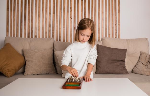 Een klein blond meisje zit aan een tafel en speelt schaak in een kamer