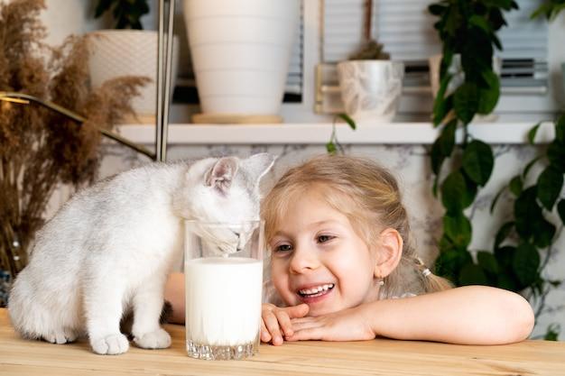 Een klein blond meisje zit aan een tafel met een wit schots katje glimlacht en kijkt toe als het katje