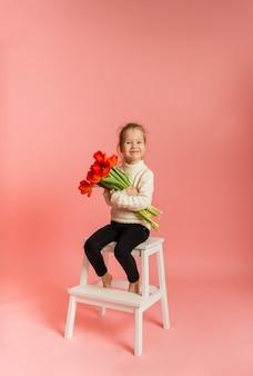 Een klein blond meisje zit op een stoel en houdt een boeket tulpen op een roze muur met een ruimte voor tekst met een kopie van de ruimte
