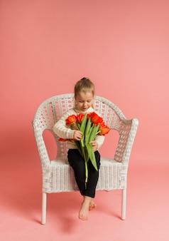 Een klein blond meisje zit op een stoel en houdt rode tulpen op een roze muur