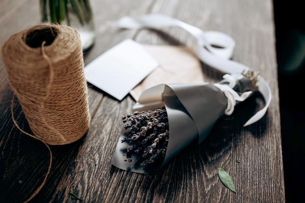 Een klein boeket bloemen verpakt in een papieren ansichtkaart envelop en een wit lint staan op tafel