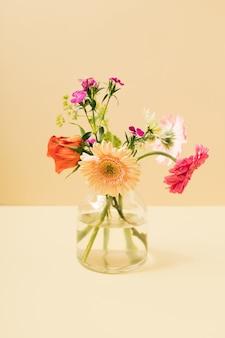 Een klein boeket lentebloemen in een glazen vaas tegen een gele achtergrond. zomer lay-out met kopie ruimte.