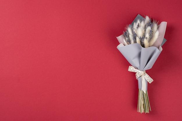Een klein boeket van lavendel met lagurusn rode achtergrond met kopie ruimte.