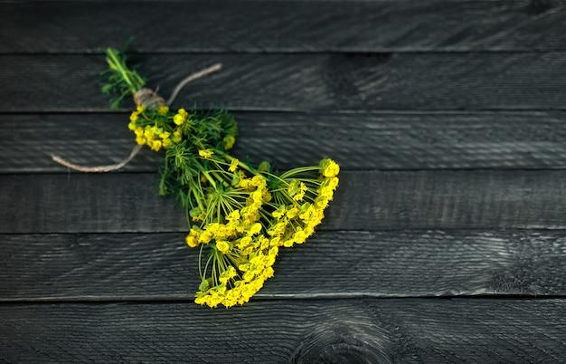 Een klein boeket wilde bloemen is vastgebonden met een touw en ligt op een houten achtergrond.