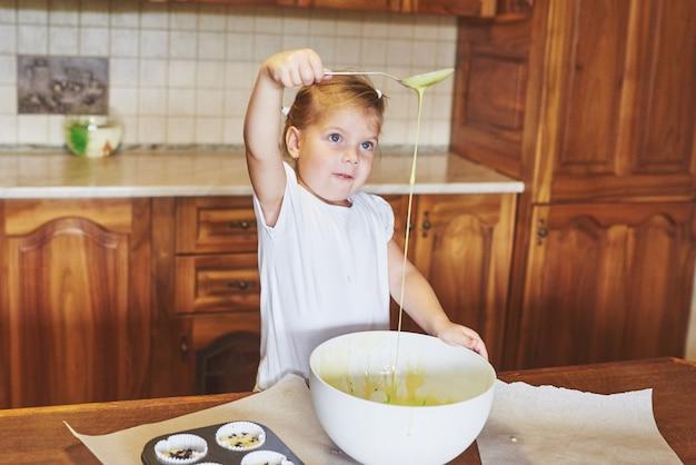 Een klein braaf meisje bakt lekkere cupcakes