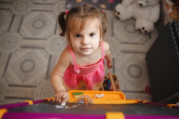 Een klein brunette meisje met twee paardenstaarten thuis in de speelkamer in de buurt van het bord met krijt in haar handen.