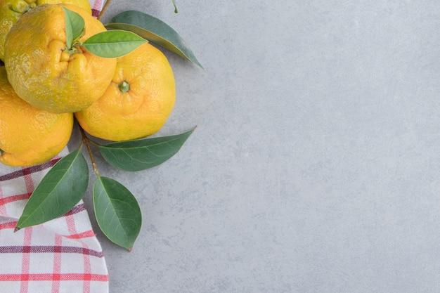 Een klein bundeltje mandarijnen op een handdoek op marmer.