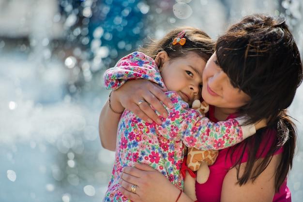 Een klein charmant meisje omhelst haar moeder in het park bij de fontein