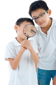 Een klein chinees jongetje en zijn broer turen naar de camera door een vergrootglas, geïsoleerd op een witte achtergrond