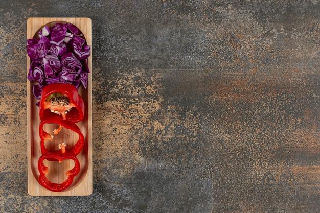 Een klein deel fijngesneden kool en gesneden peper, op het marmeren oppervlak