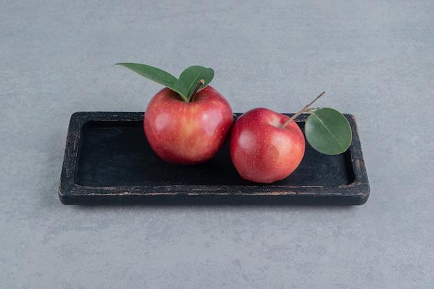 Een klein dienblad met sappige appels op marmer