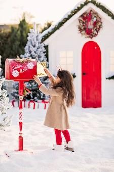 Een klein donkerbruin meisje in een beige jas en een rode lengtegraad stuurt een brief naar de kerstman in een rode brievenbus.