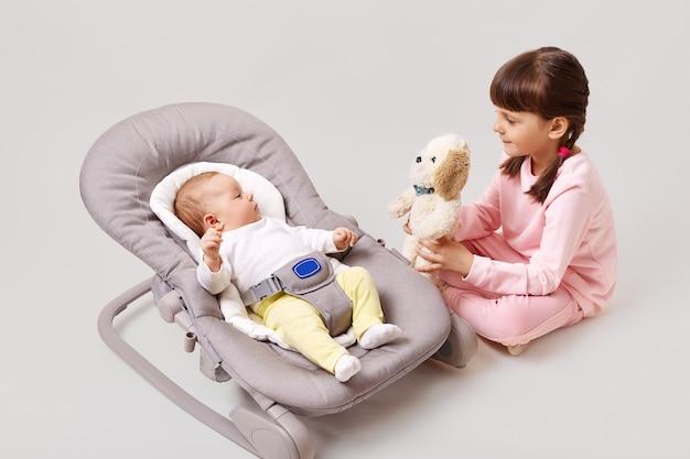 Een klein donkerharig meisje met vlechtjes speelt met haar pasgeboren zusje of broer die in een babyschommelstoel ligt