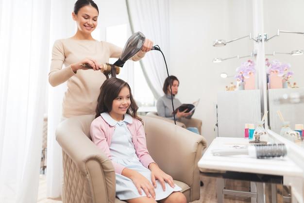 Een klein donkerharig meisje zit in de stoel van de schoonheidssalon
