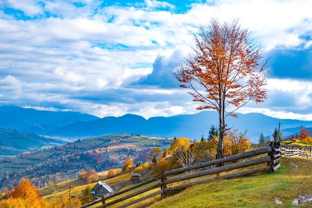 Een klein dorpje onder fantastische heuvels bedekt met kleurrijke herfstbossen