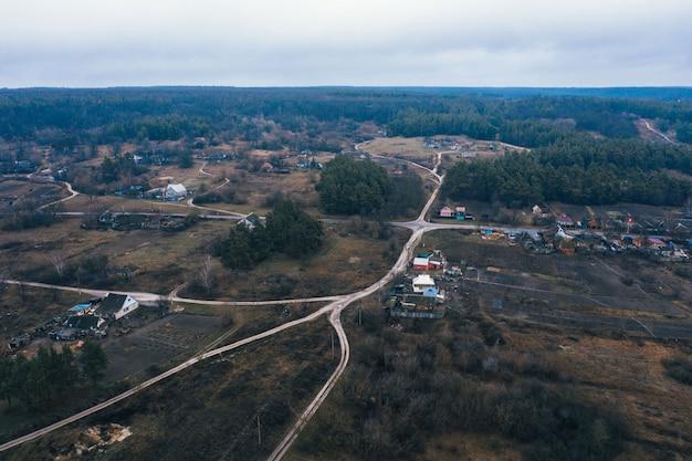 Een klein dorpje op een vlakte tussen het bos. landelijk landschap in de sneeuwloze winter. luchtfoto.