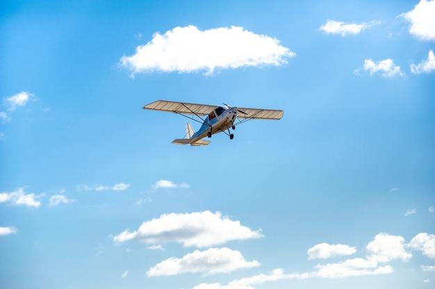 Een klein eenmotorig vliegtuig dat overvliegt tegen de blauwe lucht.