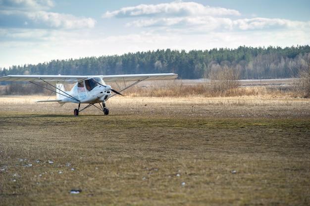 Een klein eenmotorig vliegtuig maakt een landing op de grond.