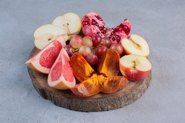 Een klein fruitassortiment op een houten bord op marmeren achtergrond.